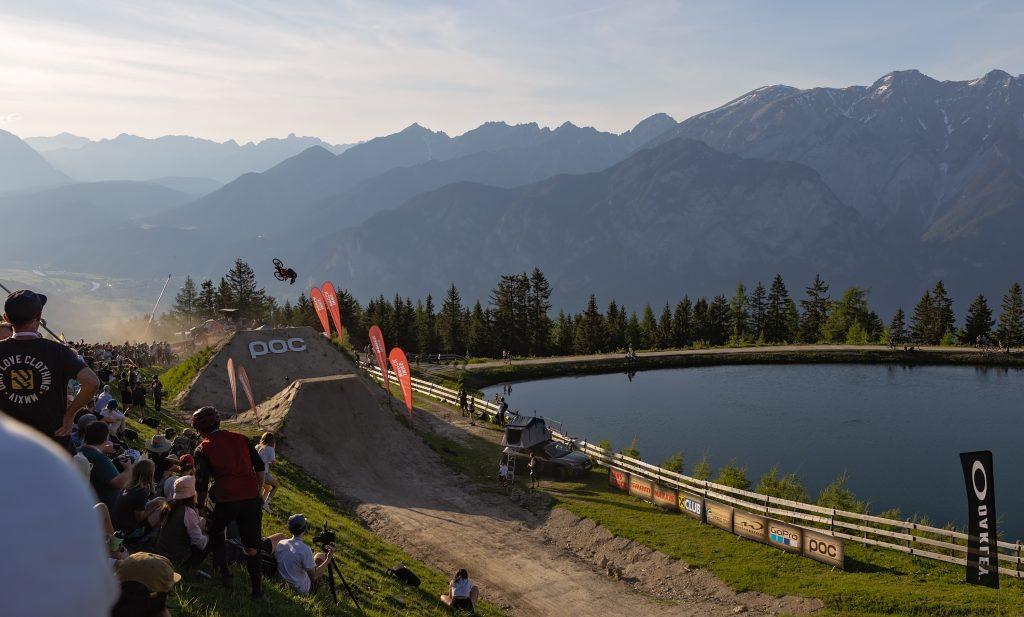 A mountain biker does a flip off of a ramp at Crankworx Innsbruck 2021.
